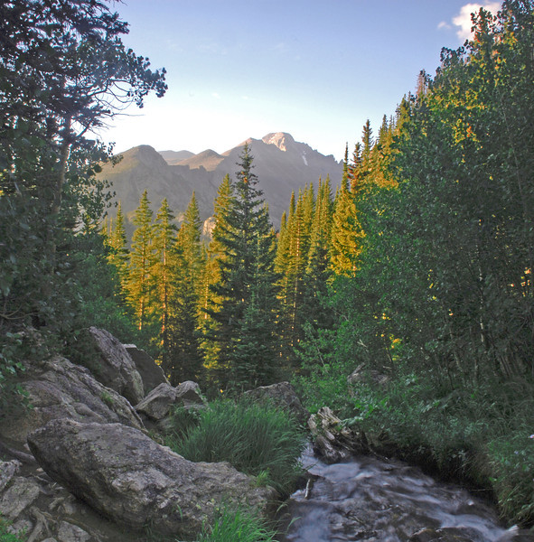 A rushing mountain stream  points the way to mighty Long's Peak.