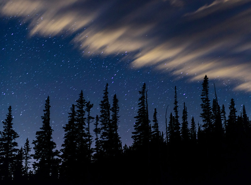 Deep in  Wild Basin the winds blow off a cloud cover to reveal the night stars.