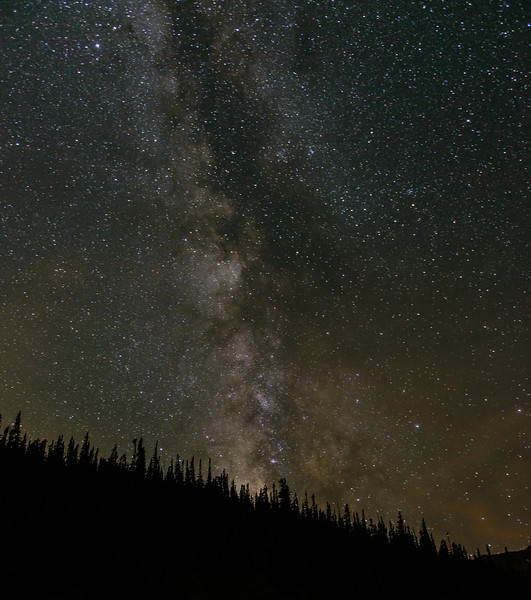 The Milky Way fills the night sky above a ridge in Wild Basin.