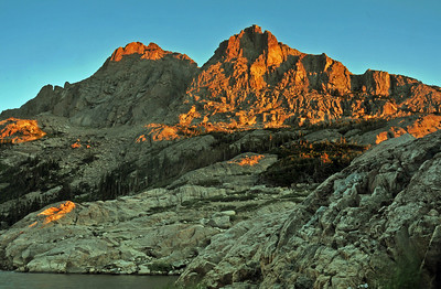 Above the shores of Bluebird Lake the first light of a new day burns the peaks of the continental divide with alpen glow.