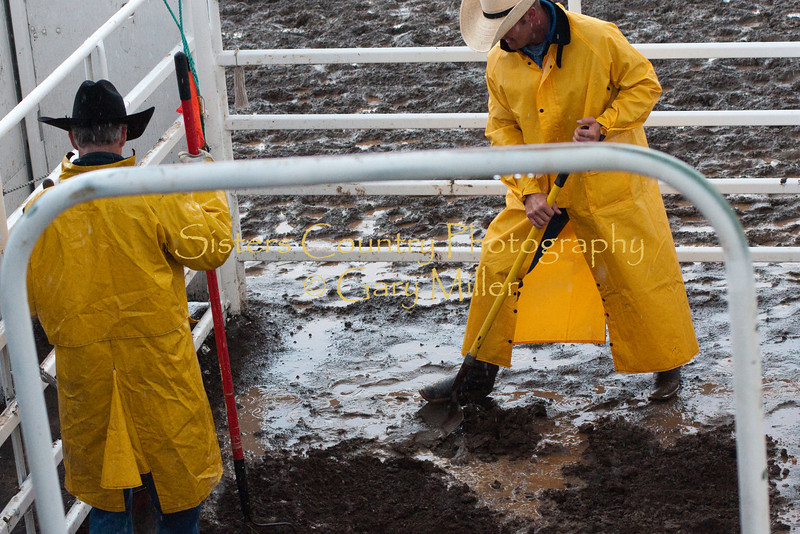 Digging a drainage canal in the flooded chutes of the Sisters Rodeo Friday night.