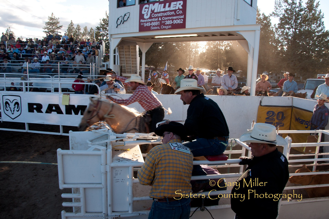 A steer wrestler barrels out of the gate as the sun sinks to the horizon. Friday evening, Sisters Rodeo 2010 Sisters Country Photography