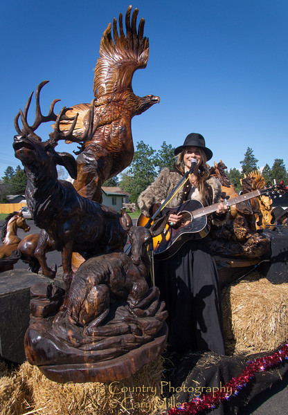 Anastacia is another beautiful piece of artwork as she plays music nestled in the fantastic wood scultptures of her husband, renowned artis J. Chester (Skip) Armstrong on their award winning entry at the Sisters Rodeo Parade 2012 - Sisters, Oregon - Gary N. Miller - Sisters Country Photography