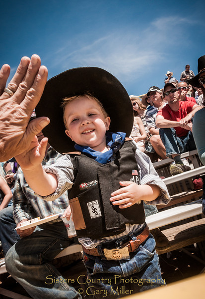 This cowpoke is getting a high five from Sisters Rodeo Photographer Gary Miller on Sunday, a picture perfect day at the 2012 Sisters Rodeo -Sisters, Oregon - Gary N. Miller - Sisters Country Photography