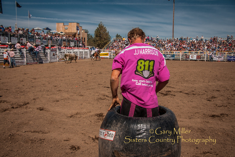 J.J. Harrison, PRCA Rodeo Clown extrordinaire, gets a lot of rock and a big roll into the fence from one big mean bull. J.J. manages to give photographer Gary Miller the big thumbs up at the end letting  the crowd know he was OK. - Sunday, a picture perfect day at the 2012 Sisters Rodeo -Sisters, Oregon - Gary N. Miller - Sisters Country Photography