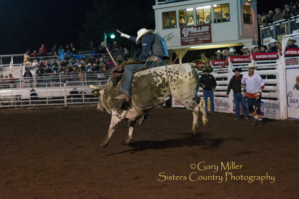 Bullrider Brent Menz's spur on his boot gets caught on the strap still attached to this powerful and dangerous bull for a hair-raising finish to a fantastic ride - Quick action and escue heroics are by top flight PRCA bullfighters Danny Newman & Rowdy Barry assisted by arena professionals - Friday Night at the 2012 Sisters Rodeo -Sisters, Oregon - Gary N. Miller - Sisters Country Photography