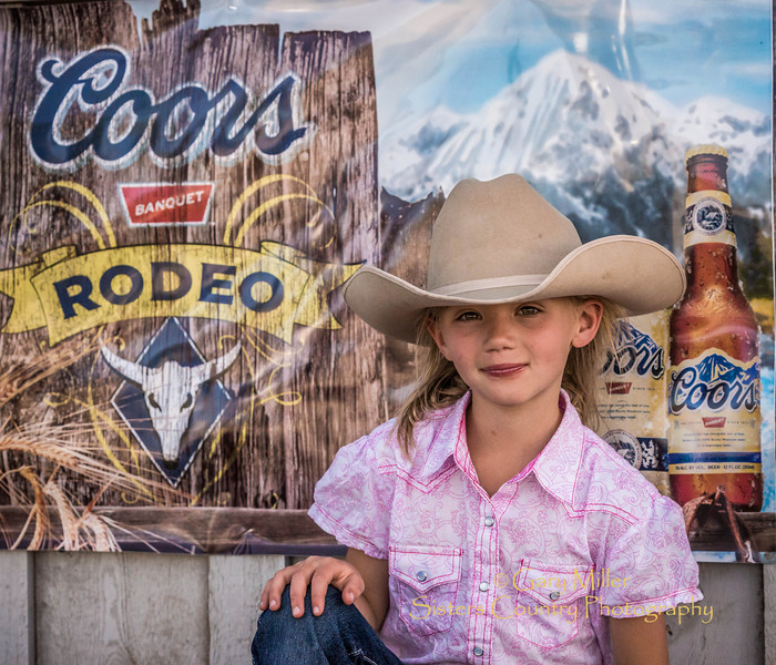 Young cowgirl enjoying a 'Coors Moment'. You don't have to drink it to like what it's doing for your day . Wednesday Bull Extravaganza night at the 2013 Sisters Rodeo - Sisters, Oregon - Copyright © 2013 Gary N. Miller, Sisters Country Photography