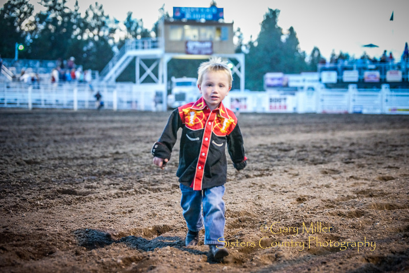 Young cowboy returns from meeting with his buddy JJ the rodeo clown. Xtreme Bulls night at the 2014 Sisters Rodeo - Sisters, Oregon © 2014 Gary N. Miller, Sisters Country Photography