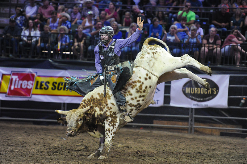 Justin Hendrix rides on Mud Packet during the Bull Riding event at the Larimer County Fair Rodeo in Loveland on Aug. 8, 2016. Hendrix was disqualified early in his ride for touching the bull with his free hand.<br /> <br /> Photo by Michael Ortiz/ Loveland Reporter-Herald