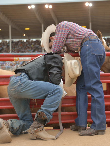 Justin Sheely | The Sheridan Press<br /> Bareback rider Hunter Carlson, left, and friend Lane McGehee put the rigging on a horse named Exotic Blond during the Sheridan WYO Rodeo Saturday at the Sheridan County Fairgrounds.