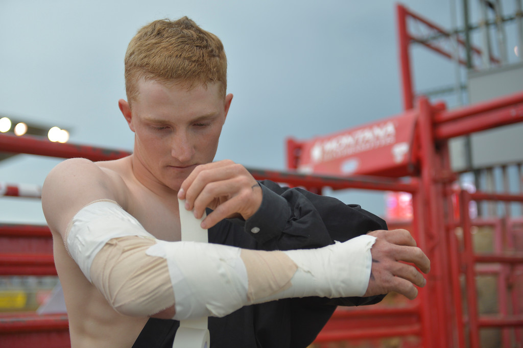 Justin Sheely | The Sheridan Press<br /> Local rodeo athlete Hunter Carlson uses tape to lock his right elbow in preparation for bareback riding during the Sheridan WYO Rodeo Saturday at the Sheridan County Fairgrounds.