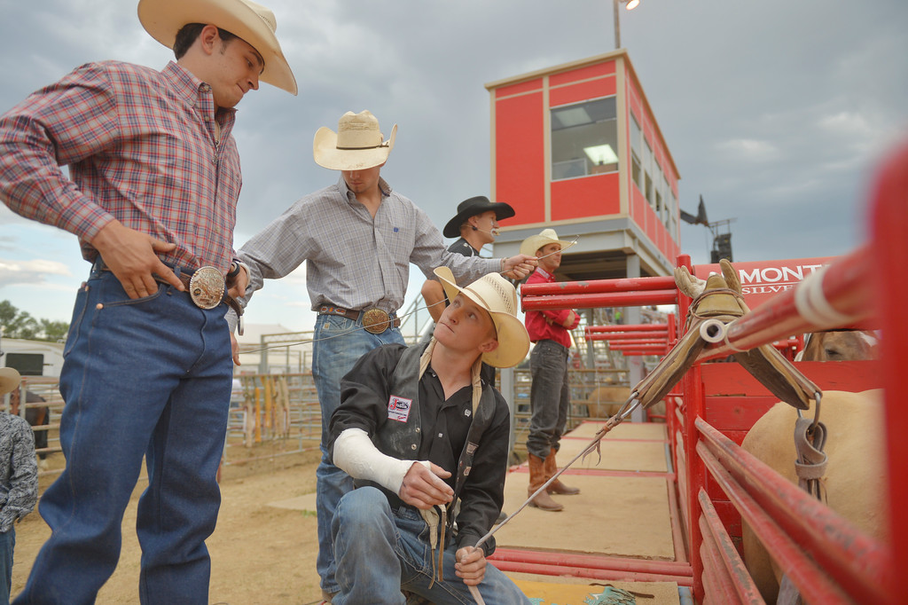 Justin Sheely | The Sheridan Press<br /> Rodeo friends Lane McGehee, left, and Paden Hurst look on as bareback rider Hunter Carlson prepares his rigging during the Sheridan WYO Rodeo Saturday at the Sheridan County Fairgrounds.