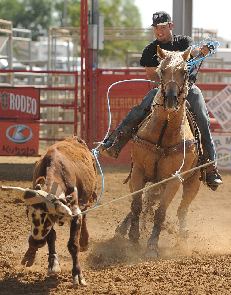 Mike Dunn | The Sheridan Press<br /> Riley Curuchet, of Kaycee, goes for the heel of a calf during the Bob King Memorial Roping Sunday at the Sheridan County Fairgrounds. The annual event includes team ropers from across the region and pays respect to famous cowboy and rope maker Bob King.