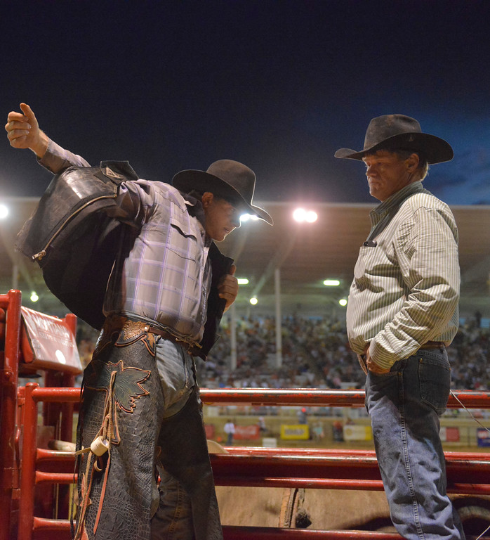 Justin Sheely | The Sheridan Press<br /> Sheridan bull rider Tell Kolbod puts his vest on as father Steve Kobold looks on during the Sheridan WYO Rodeo Saturday at the Sheridan County Fairgrounds.