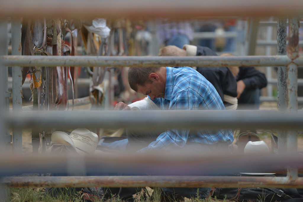 Justin Sheely | The Sheridan Press<br /> Bareback riding athletes bow for a prayer during the Sheridan WYO Rodeo Saturday at the Sheridan County Fairgrounds.