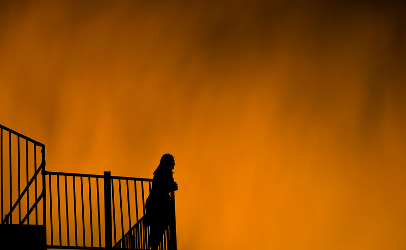 Justin Sheely | The Sheridan Press<br /> A woman watches the action as the sunset lights rain clouds during the Sheridan WYO Rodeo Saturday at the Sheridan County Fairgrounds.