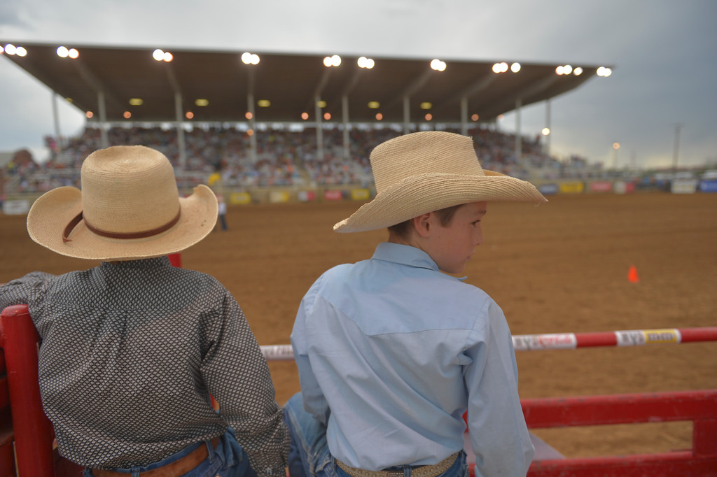 Justin Sheely | The Sheridan Press<br /> Cooper Justice and Gabe Purdum hang out at the bucking chutes during the Sheridan WYO Rodeo Saturday at the Sheridan County Fairgrounds.
