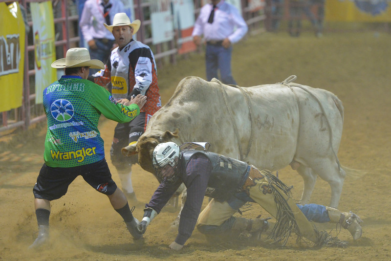 Justin Sheely | The Sheridan Press<br /> Bull fighters Joe Butler, left, and Nate Justice distract the bull as rider Riker Carter of Stone Idaho, gets up during the Sheridan WYO Rodeo Saturday at the Sheridan County Fairgrounds.