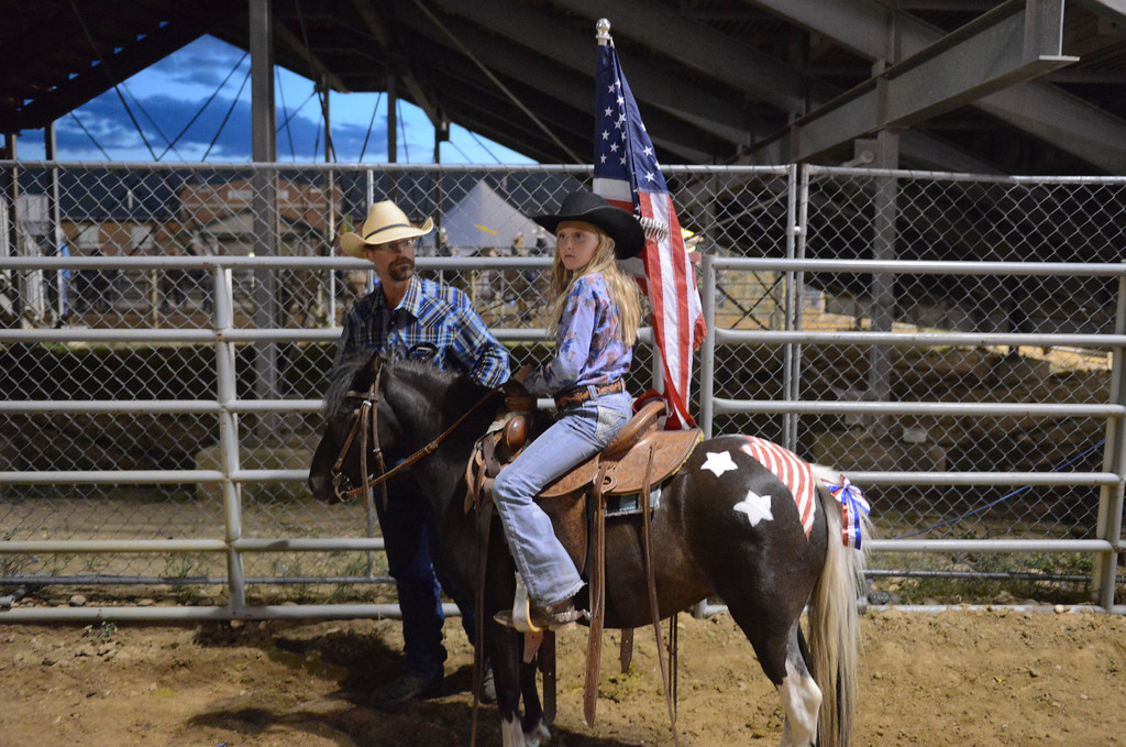 Justin Sheely | The Sheridan Press<br /> Nine-year-old Grace VanDyke waits with her father Paul VanDyke before she rides old glory in to the arena during the Sheridan WYO Rodeo Saturday at the Sheridan County Fairgrounds.