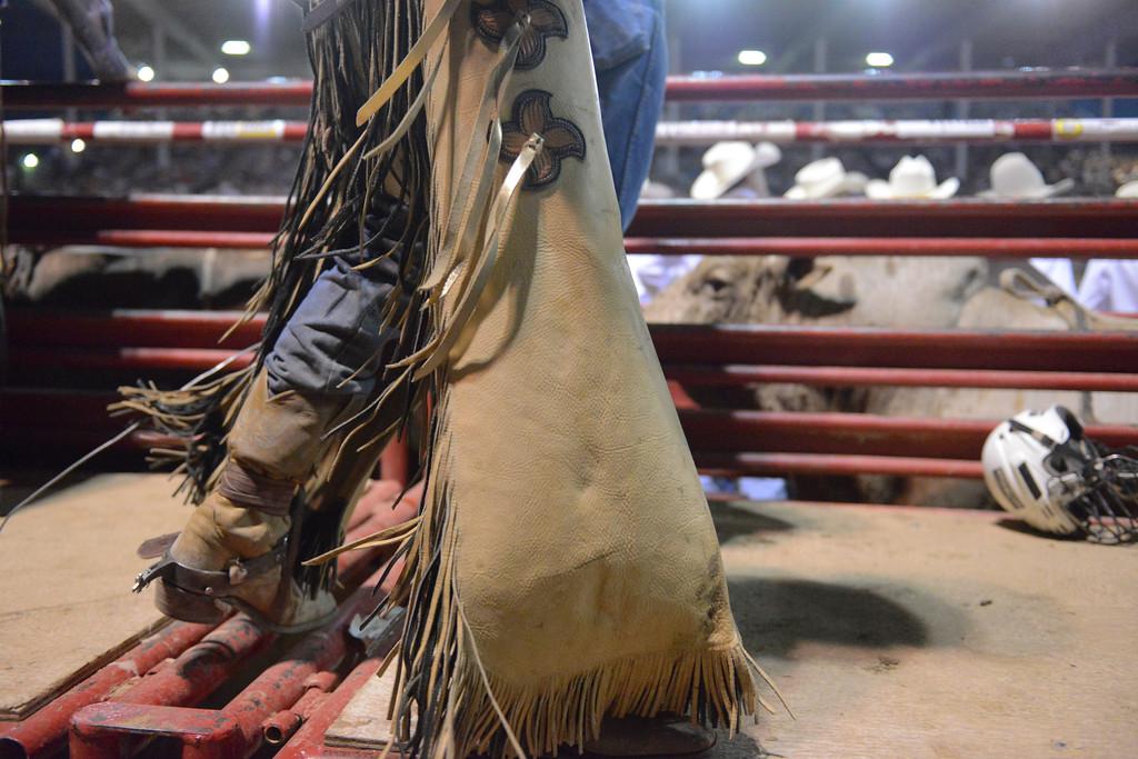 Justin Sheely | The Sheridan Press<br /> A bull rider walks behind the bucking chutes during the Sheridan WYO Rodeo Saturday at the Sheridan County Fairgrounds.