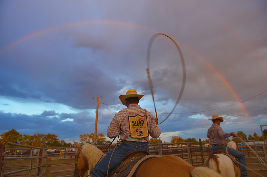 Justin Sheely | The Sheridan Press<br /> Steer ropers warm up as a rainbow is seen in the eastern sky during the Sheridan WYO Rodeo Saturday at the Sheridan County Fairgrounds.