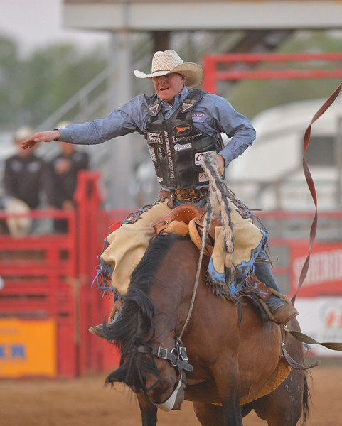 Justin Sheely | The Sheridan Press<br /> Taos Muncy of Corona, New Mexico competes in saddle bronc riding during the Sheridan WYO Rodeo Wednesday at the Sheridan County Fairgrounds.