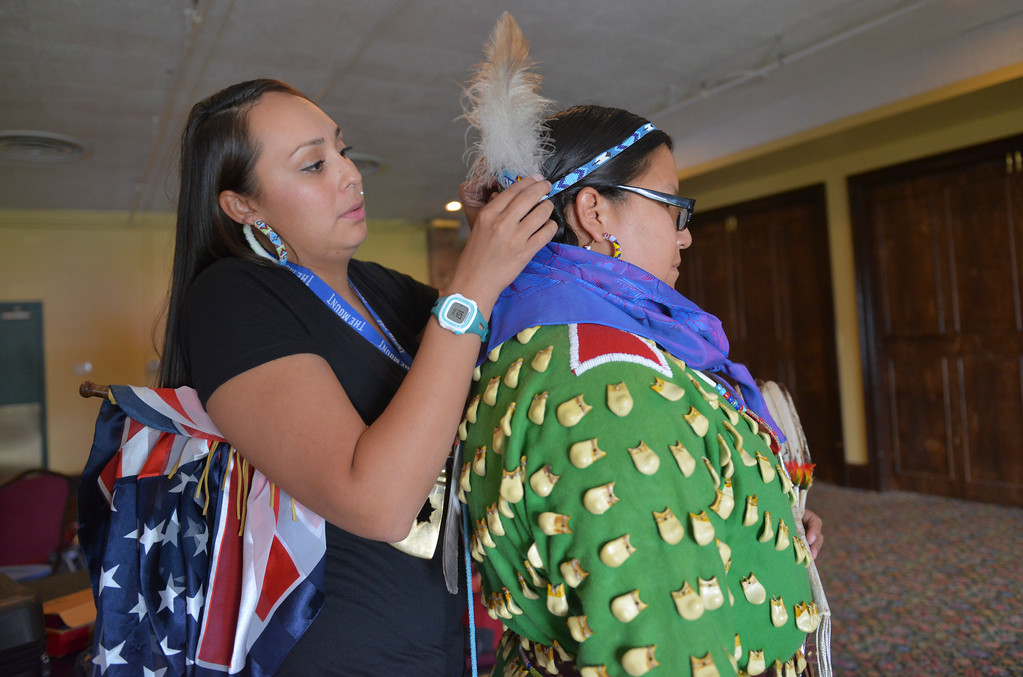 Justin Sheely | The Sheridan Press <br /> Coty Real Bird helps Hayley Blaine get ready for the First People's Powwow Wednesday at the Historic Sheridan Inn. The culminating event is Friday after the Sheridan WYO Rodeo Parade.