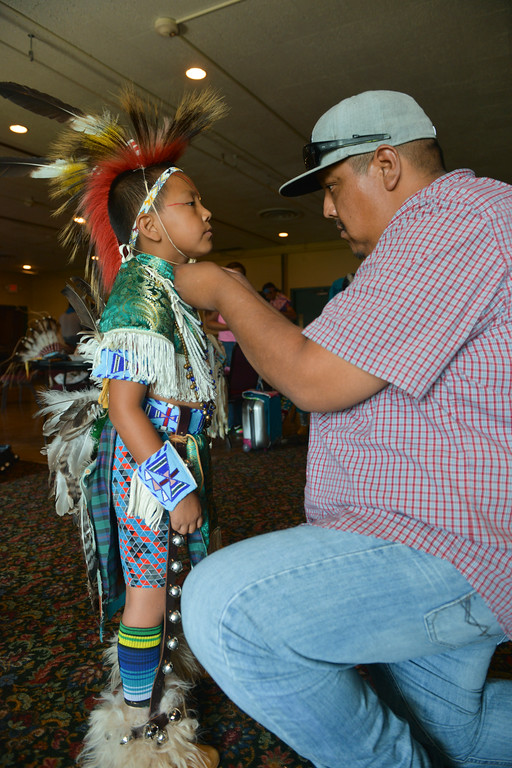 Justin Sheely | The Sheridan Press <br /> Shann Iron ties a roach on his son Blake Iron, 7, in preparation for the First People's Powwow Wednesday at the Historic Sheridan Inn. The culminating event is Friday after the Sheridan WYO Rodeo Parade.