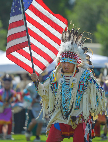 Justin Sheely | The Sheridan Press <br /> United States veteran Taylor Real Bird carries the national flag during the First People's Powwow Wednesday at the Historic Sheridan Inn. The culminating event is Friday after the Sheridan WYO Rodeo Parade.