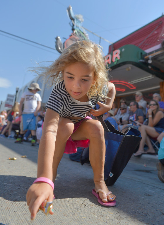 Justin Sheely | The Sheridan Press<br /> Six-year-old Stella Stroud picks up candy during the Sheridan WYO Rodeo Parade Friday morning on Main Street.