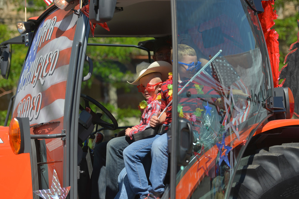 Justin Sheely | The Sheridan Press<br /> Children ride in a tractor during the Sheridan WYO Rodeo Parade Friday morning on Main Street.