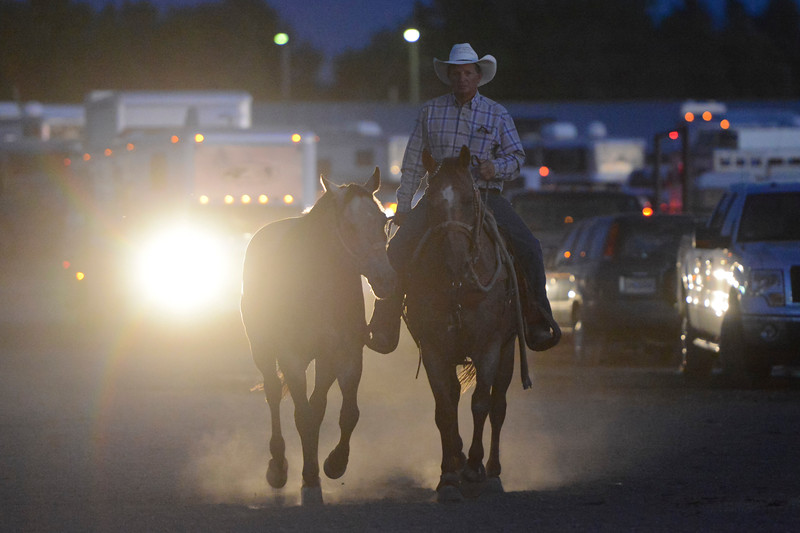 Justin Sheely | The Sheridan Press<br /> A cowboy leads a horse behind the arena during Thursday's Sheridan WYO Rodeo at the Sheridan County Fairgrounds.
