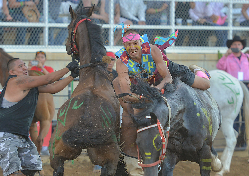 Justin Sheely | The Sheridan Press<br /> John Redman of team Umitilla Express, Dendleton, Oregon, collides with a jockey and horse from Bad War Deeds of Wyola, Montana, in the second heat of the Indian Relay Races during Thursday's Sheridan WYO Rodeo.
