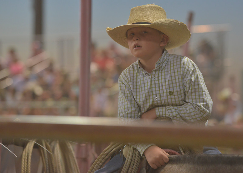 Justin Sheely | The Sheridan Press<br /> Eight-year-old Kannon Gilbert of Encampment, Wyoming, sits on his horse behind the bucking chutes during Thursday's Sheridan WYO Rodeo at the Sheridan County Fairgrounds.