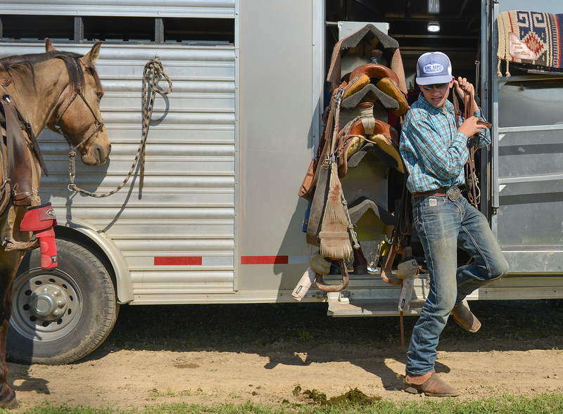 Justin Sheely | The Sheridan Press<br /> Will Albrecht hauls bits and bridles from a friend's horse trailer during the Sheridan High School Rodeo at the Sheridan County Fairgrounds Saturday, May 26, 2018.