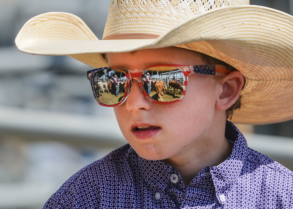 Justin Sheely | The Sheridan Press<br /> Nine-year-old Tate Leno helps with sorting the steers behind the chute during the Sheridan High School Rodeo at the Sheridan County Fairgrounds Saturday, May 26, 2018.