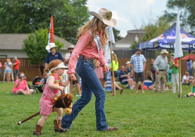 Justin Sheely | The Sheridan Press<br /> Two-year-old Adelena Woods is guided by Sheridan WYO Rodeo Queen Hannah Ostheimer for the stick horse races during the Sheridan WYO Rodeo Boot Kickoff at Whitney Commons Park Tuesday, July 10, 2018.