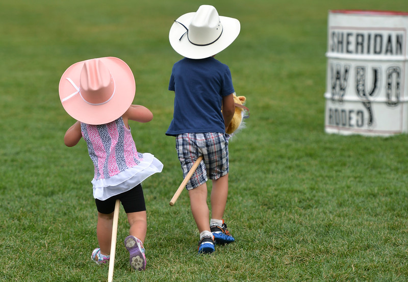 Justin Sheely | The Sheridan Press<br /> Three-year-old Natalie Filkins, left, races her brother Jaxon Filkins, 5, in stick horse barrel racing during the Sheridan WYO Rodeo Boot Kickoff at Whitney Commons Park Tuesday, July 10, 2018.