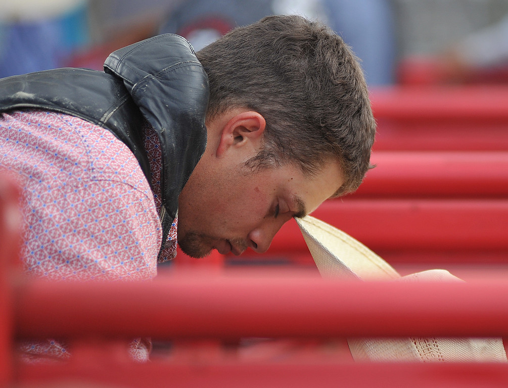 Ben Longhofer takes a moment to pray before competing in Bull Riding Saturday afternoon during the Sheridan County Rodeo at the Sheridan County Fairgrounds. (Justin Sheely/The Sheridan Press)