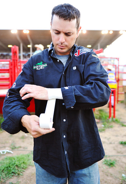 Wesley Silcox, of Payson, Utah, tapes up his wrists in preparation for Bull Riding competition Thursday at the Sheridan-Wyo-Rodeo. Silcox said that he had broken his wrists twice during his career, and does not want that to happen again. (Justin Sheely/The Sheridan Press)