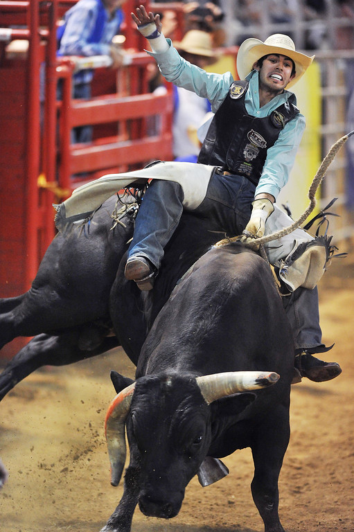 Tim Bingham, from Honeyville, Utah, holds onto Mayhem during Bull Riding competition in Saturday's Sheridan-Wyo-Rodeo. Bingham received a no-score after falling off early.(Justin Sheely/The Sheridan Press)