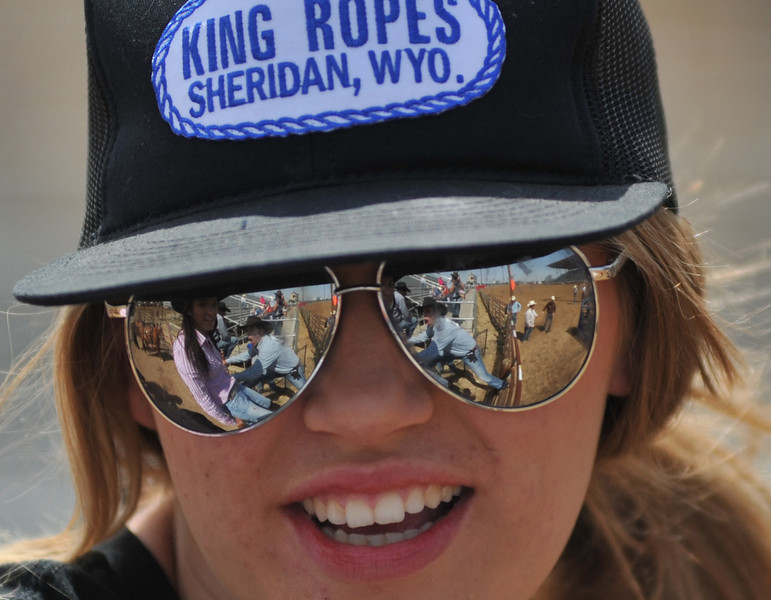 Shelby Mann, 17, looks at her friends through her sunglasses as they watch the Sheridan County Rodeo Saturday at the Sheridan County Fairgrounds. (Justin Sheely/The Sheridan Press)