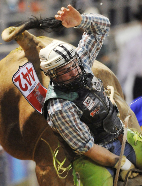 Kris Newman, of Casper, Wyo., competes in Bull Riding Saturday in the Sheridan-Wyo-Rodeo at the Sheridan County Fairgrounds arena. Newman later fell off the bull for a no-score. (Justin Sheely/The Sheridan Press)