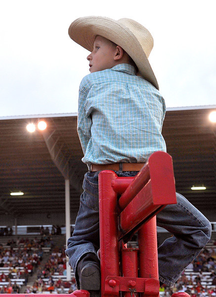 Nick Albrecht, 8, sits on the horse chutes to get a front row view of Thursday's Sheridan-Wyo-Rodeo performance at the Sheridan County Fairgrounds. (Justin Sheely/The Sheridan Press)
