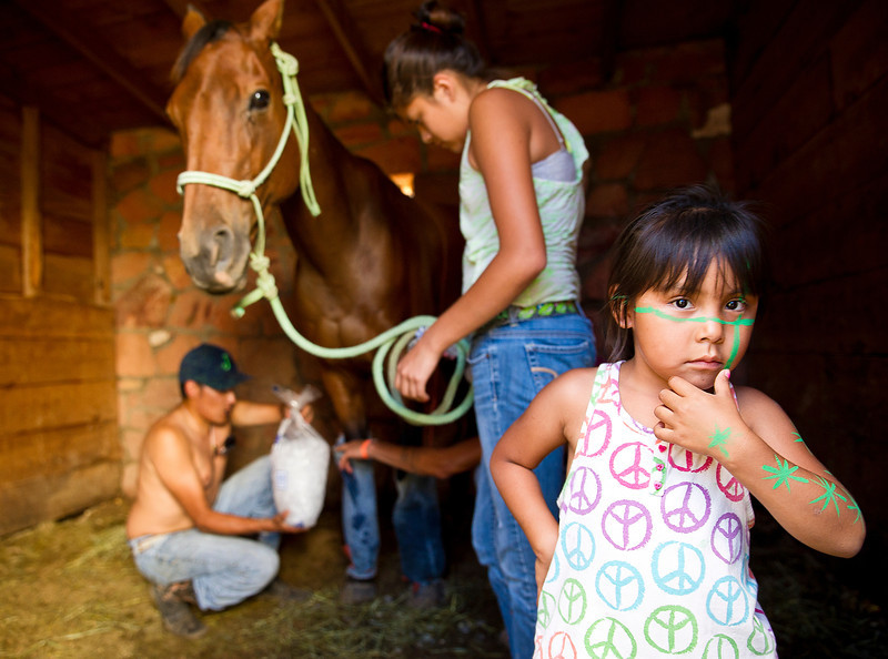 4-year-old Jaelyn He Does It, right, shows off her new face painting as her family ices down a horse's legs in the stalls Thursday before the World Champion Indian Relay Races at the Sheridan County Fairgrounds. (Justin Sheely/The Sheridan Press)