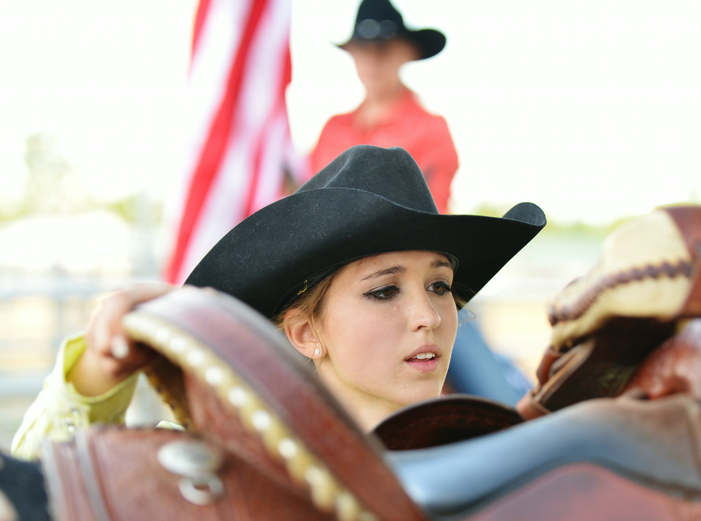 Senior Princess Contestant Alanna Starkovich adjusts the saddle on her horse during the Rodeo Royalty horsemanship competition Saturday evening at the Sheridan County Fairgrounds.