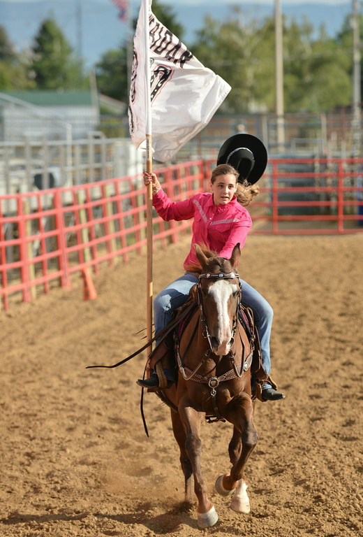 Twelve-year-old Ashlyn Ibach carries the flag during the Rodeo Royalty horsemanship competition Saturday evening at the Sheridan County Fairgrounds.