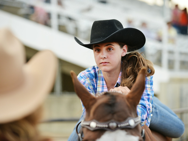 Twelve-year-old Ashlyn Ibach rests on her horse as other contests compete during the Rodeo Royalty horsemanship competition Saturday evening at the Sheridan County Fairgrounds.