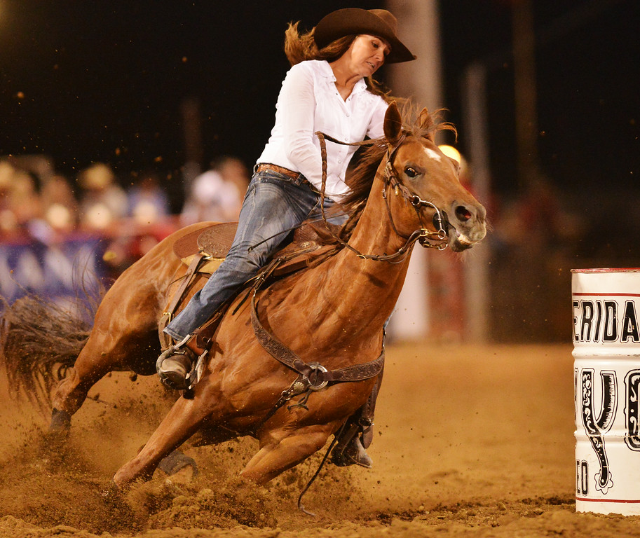 Kelli Thouvenell of Hooper, Utah, turns her horse in the barrel racing event during the Sheridan WYO Rodeo Thursday night at the Sheridan County Fairgrounds. The Sheridan Press|Justin Sheely.