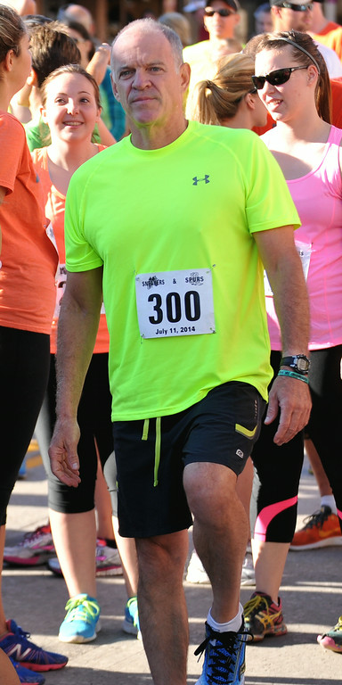 Michael Merrill warms up his legs before running in the Sneakers and Spurs Rodeo 5K on Friday in downtown Sheridan. The Sheridan Press|Mike Pruden